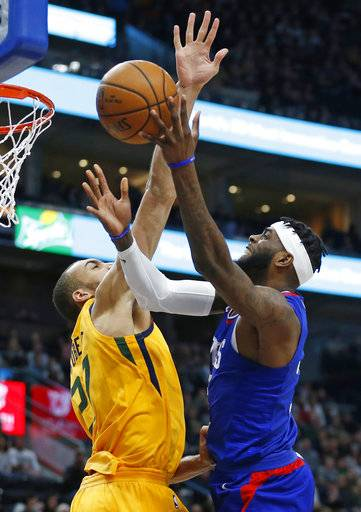 Los Angeles Clippers center Willie Reed (35) lays the ball up as Utah Jazz center Rudy Gobert (27) defends in the first half during an NBA basketball game Saturday, Jan. 20, 2018, in Salt Lake City.