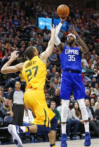 Los Angeles Clippers center Willie Reed (35) shoots as Utah Jazz center Rudy Gobert (27) defends in the first half during an NBA basketball game Saturday, Jan. 20, 2018, in Salt Lake City.