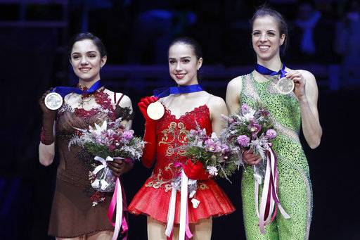 Russia's Alina Zagitova shows her gold medal, center, as she poses with Russia's silver medallist Evgenia Medvedeva, left, and Italy's bronze medallist Carolina Kostner, right, after the ladies free skating event at the European figure skating championships in Moscow, Russia, Saturday, Jan. 20, 2018.