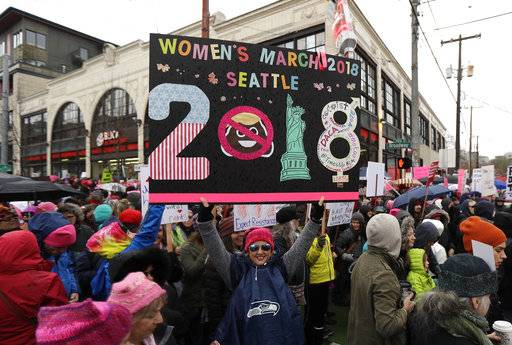 A woman holds as sign as she takes part in a Women's March in Seattle, Saturday, Jan. 20, 2018. The march was one of dozens planned across the U.S. over the weekend. (AP Photo/Ted S. Warren)