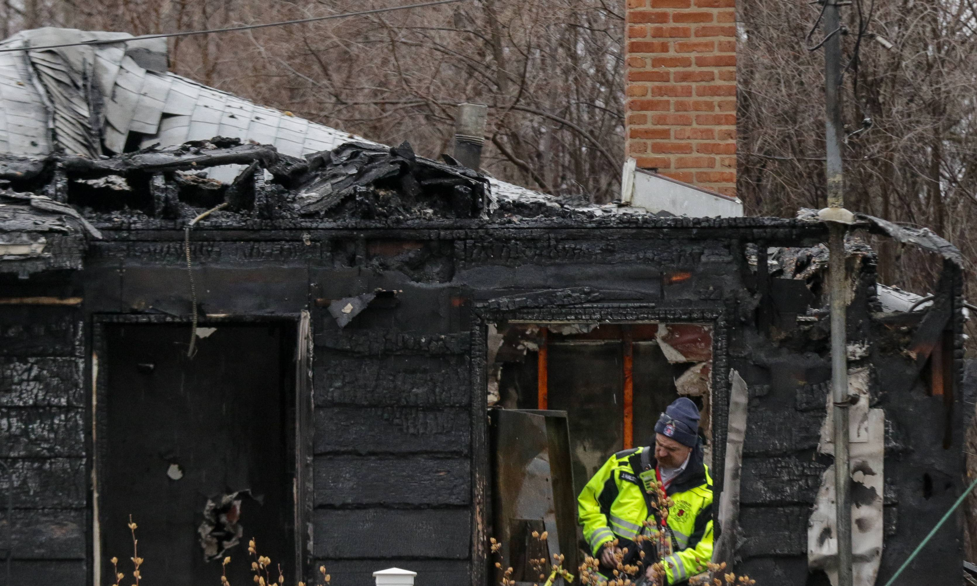 Firefighters investigate the aftermath of a fatal fire in the 700 block of Ellsworth Avenue in Addison on Monday.