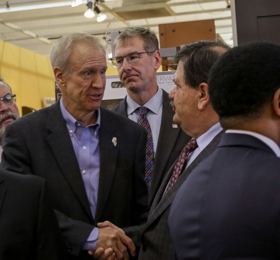 Gov. Bruce Rauner speaks with Hanover Park Mayor Rod Craig as he rallied Republicans in DuPage County Monday at Great Western Flooring in Naperville, owned by Naperville Mayor Steve Chirico.