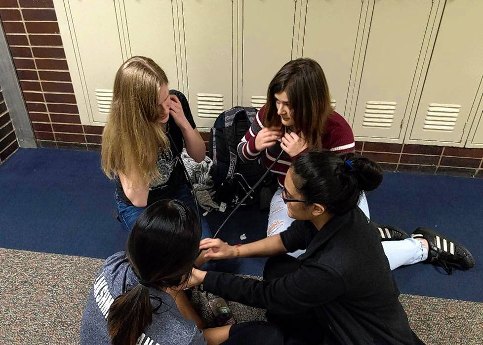 A group of students practice taking each other's blood pressure during their CNA class at Palatine High School