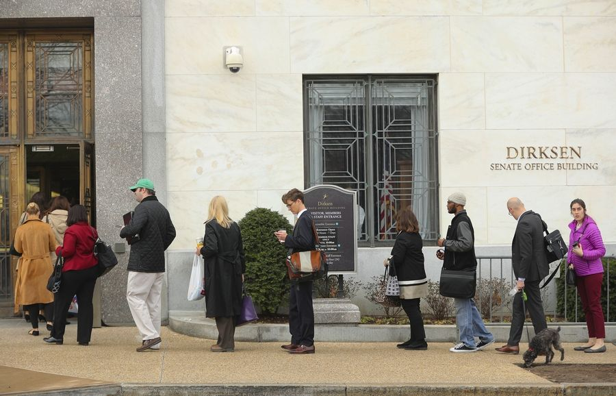 People wait in line at Dirksen Senate Office building at one of the few entrances opened for staff members at the U.S. Capitol in Washington as Day Three of the government shutdown continues on Monday, Jan. 22, 2018.