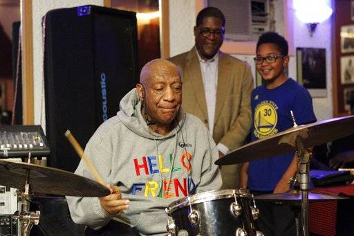 Bill Cosby plays the drums at the LaRose Jazz Club in Philadelphia on Monday, Jan. 22, 2018 as his spokesman, Andrew Wyatt, and 11-year-old drummer Mekhi Boone look on. It was his first public performance since his last tour ended amid protests in May 2015. Cosby has denied allegations from about 60 women that he drugged and molested them over five decades. He faces an April retrial in the only case to lead to criminal charges.