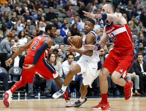 Washington Wizards' John Wall (2) and Marcin Gortat (13), of Poland, defend as Dallas Mavericks' Dennis Smith Jr. (1) drives to the basket in the second half of an NBA basketball game, Monday, Jan. 22, 2018, in Dallas.
