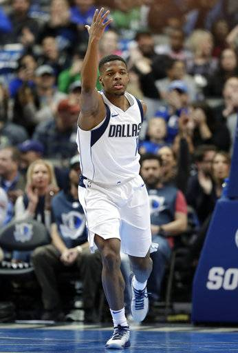 Dallas Mavericks' Dennis Smith Jr. celebrates after dunking on a breakaway play in the first half of an NBA basketball game against the Washington Wizards, Monday, Jan. 22, 2018, in Dallas.