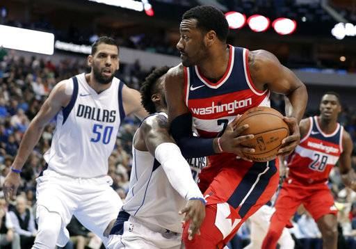 Dallas Mavericks guard Wesley Matthews, center left, and Salah Mejri (50), of Tunisia, defend as Washington Wizards' John Wall (2) works for a shot opportunity in the first half of an NBA basketball game, Monday, Jan. 22, 2018, in Dallas.