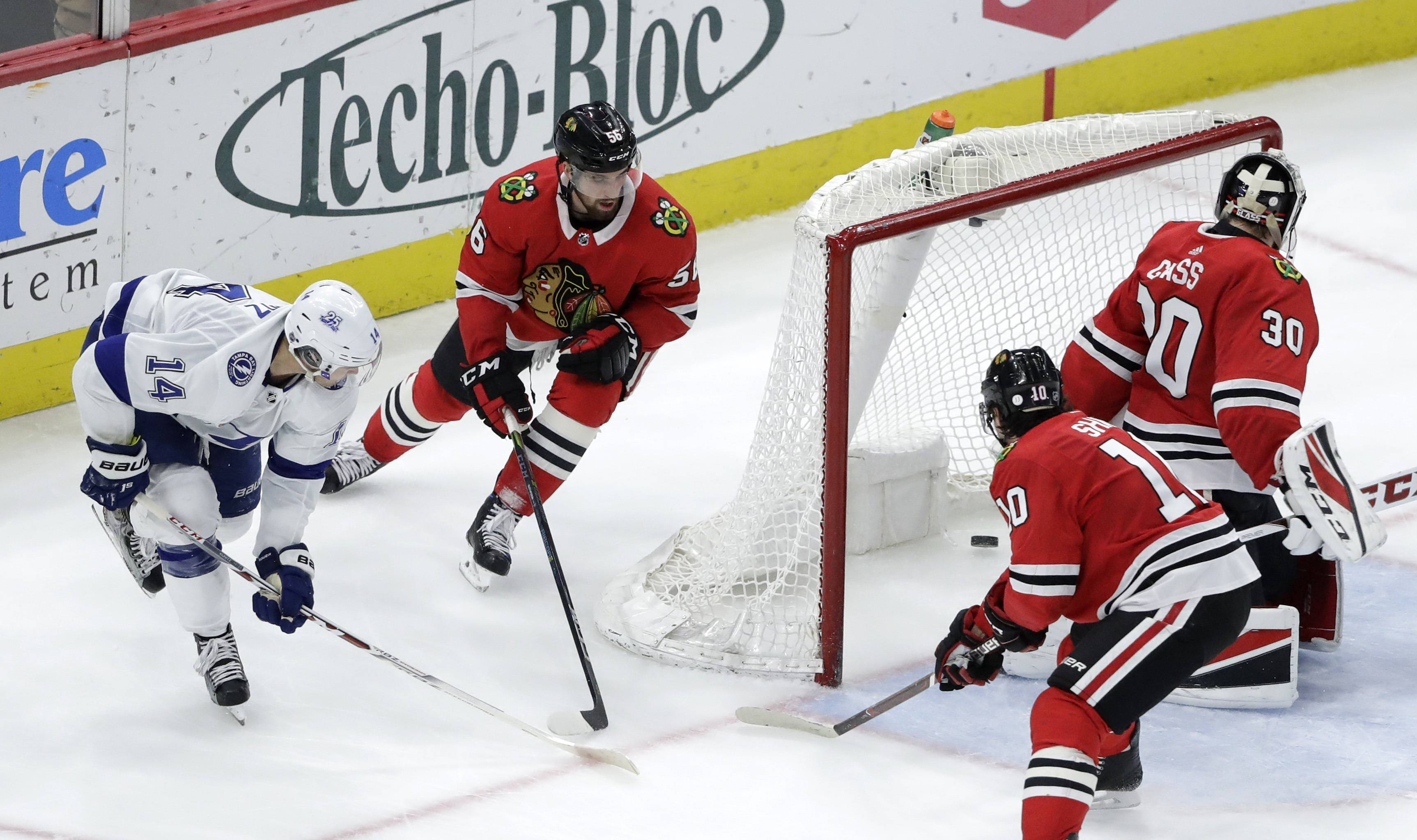 Tampa Bay Lightning's Chris Kunitz (14) scores past Chicago Blackhawks goaltender Jeff Glass as Erik Gustafsson (56) and Patrick Sharp also defend during the second period of an NHL hockey game Monday, Jan. 22, 2018, in Chicago.