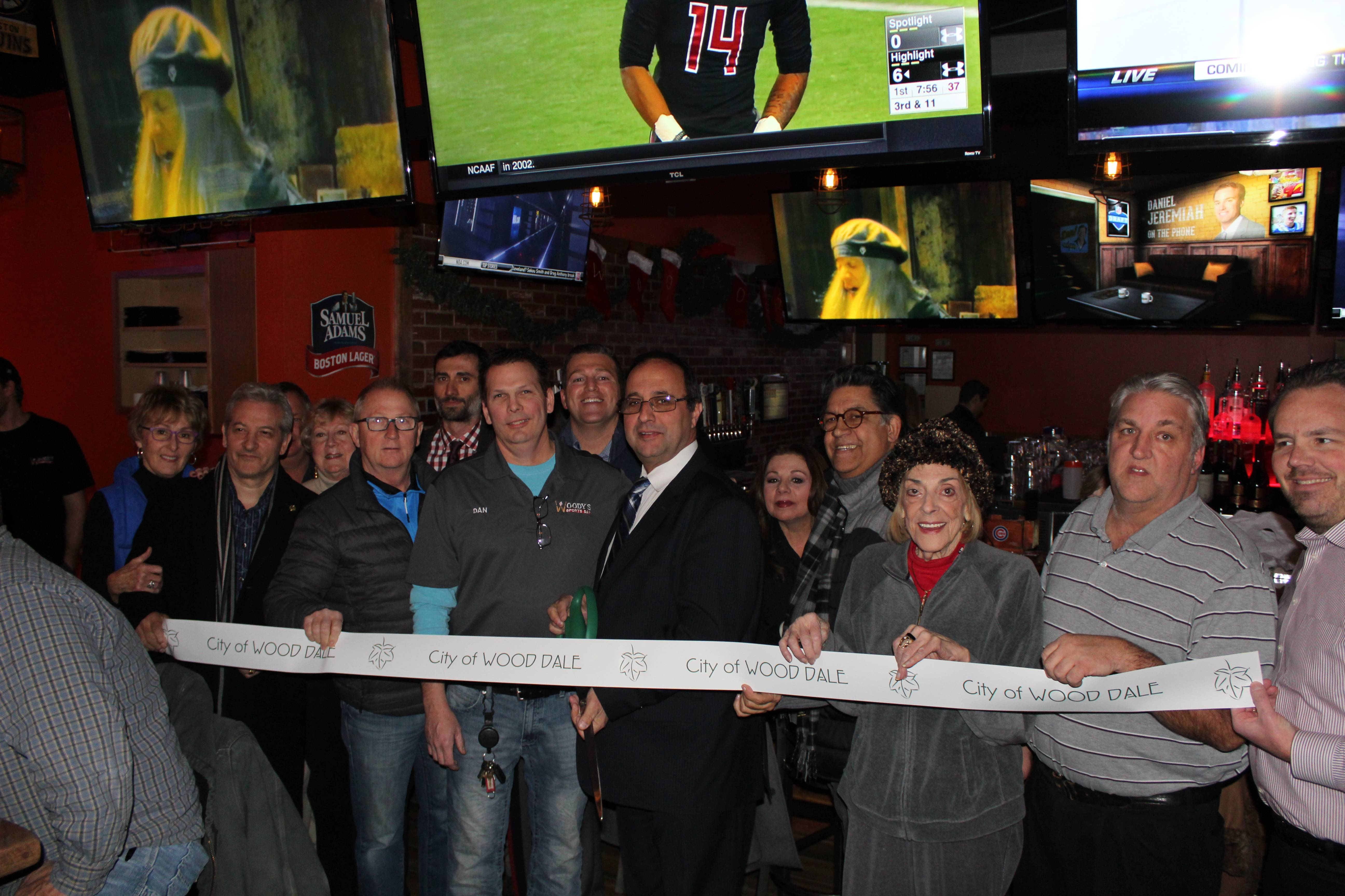 Members of the Wood Dale City Council celebrate the grand opening of Woody's Sports Bar in Wood Dale with a ribbon cutting.
