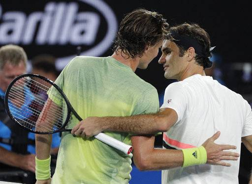 Switzerland's Roger Federer, right, is celebrated by Tomas Berdych of the Czech Republic after he won their quarterfinal at the Australian Open tennis championships in Melbourne, Australia, Wednesday, Jan. 24, 2018.