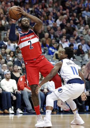 Washington Wizards guard John Wall (2) is fouled taking a shot by Dallas Mavericks' Yogi Ferrell (11) in the first half of an NBA basketball game, Monday, Jan. 22, 2018, in Dallas.