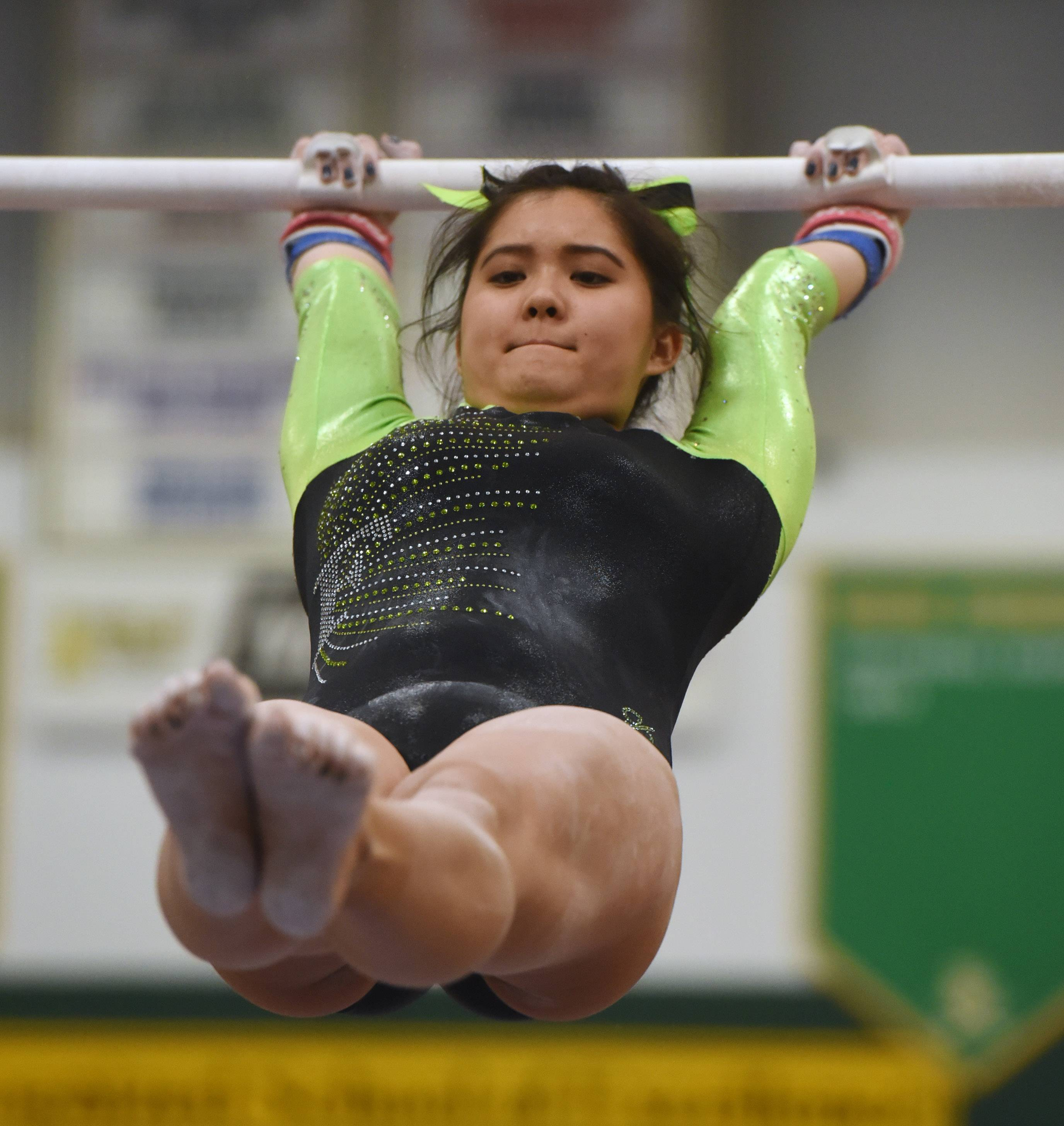 Fremd's Melanie Ng competes on the uneven parallel bars during the Mid-Suburban League girls gymnastics meet at Elk Grove on Wednesday.
