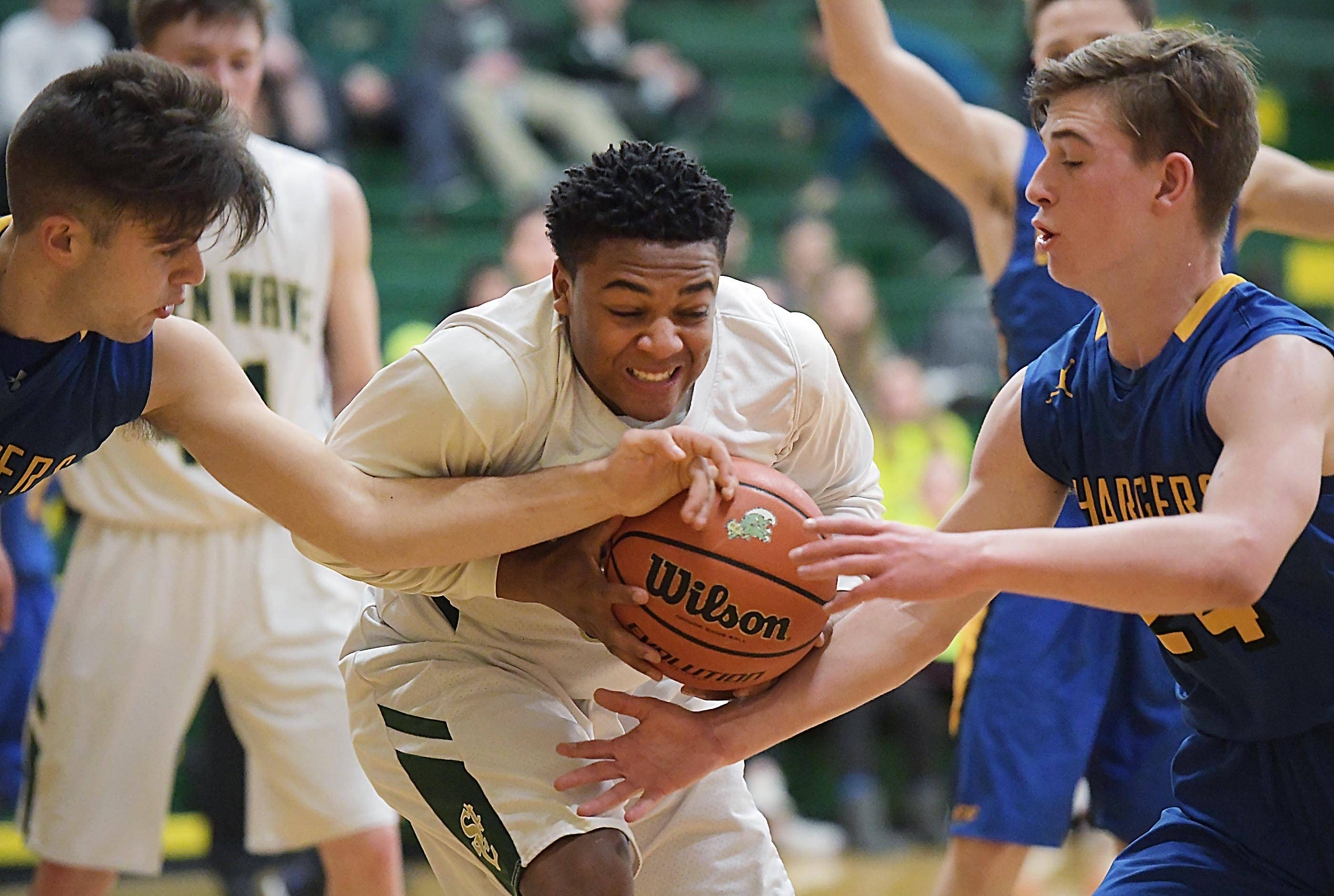 St. Edward's Sidney Muhammad struggles for control as Aurora Central Catholic's Dru Ingraham and Cameron Pedersen, right, pressure him Wednesday in a boys basketball game in Elgin.
