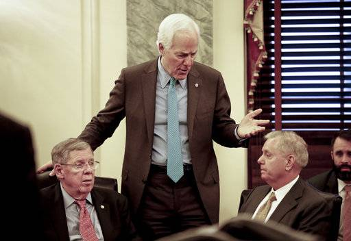 Senate Majority Whip Sen. John Cornyn, R-Texas, center, talks with Sen. Johnny Isakson, R-Ga., left, and Sen. Lindsey Graham, R-S.C., right, before the start of a meeting on immigration Wednesday, Jan. 24, 2018 on Capitol Hill in Washington. (AP Photo/Pablo Martinez Monsivais)