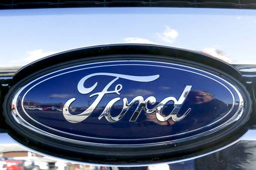 FILE - This Thursday, Nov. 19, 2015, file photo, shows the Ford badge in the grill of a pickup truck. Ford Motor Co. reports earnings, Wednesday, Jan. 24, 2018. (AP Photo/Keith Srakocic, File)