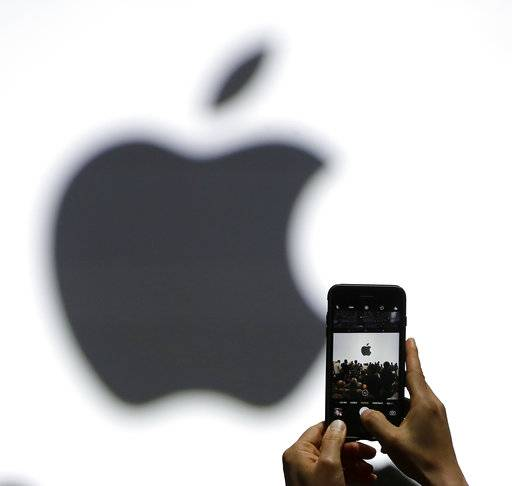 FILE - In this Monday, June 5, 2017, file photo, a person takes a photo of an Apple logo before an announcement of new products at the Apple Worldwide Developers Conference in San Jose, Calif. Apple's next major update of its mobile software will include an option that will enable owners of older iPhones to turn off a feature that slows the device to prevent aging batteries from shutting down. The free upgrade will be released in spring 2018. (AP Photo/Marcio Jose Sanchez, File)