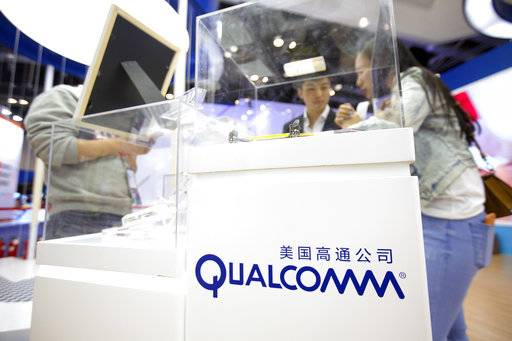 FILE - In this Thursday, April 27, 2017 file photo, visitors look at a display booth for Qualcomm at the Global Mobile Internet Conference (GMIC) in Beijing. The European Union is slapping a $1.23 billion fine on U.S. chipmaker Qualcomm for abusing its market dominance in the lucrative sector of vital components in smartphones and tablets. (AP Photo/Mark Schiefelbein, File)