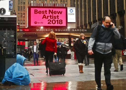 People walk near Madison Square Garden, Tuesday Jan. 23, 2018, in New York, the location for the 60th annual Grammy Awards which will be held on Sunday. (AP Photo/Bebeto Matthews)
