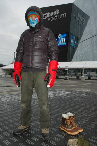 This Dec. 21, 2017 image shows Steve Schreader, who works at Midwest Mountaineering, an outdoor gear store in Minneapolis, modeling basic apparel for dressing in layers for winter, outside US Bank Stadium in Minneapolis. Schreader says layering is the key to staying warm and comfy in cold weather, whether you're attending a tailgate party in Minneapolis for Super Bowl or any other outdoor recreation. (AP Photo/Jeff Baenen)