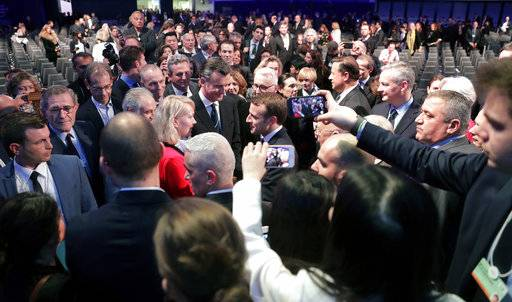 Emmanuel Macron, President of France, center, is surrounded by listeners after a special address as part of the annual meeting of the World Economic Forum in Davos, Switzerland, Wednesday, Jan. 24, 2018. (AP Photo/Markus Schreiber)