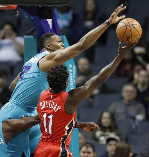 Charlotte Hornets' Dwight Howard (12) blocks a shot by New Orleans Pelicans' Jrue Holiday (11) during the first half of an NBA basketball game in Charlotte, N.C., Wednesday, Jan. 24, 2018. (AP Photo/Chuck Burton)