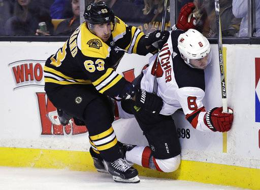 Boston Bruins left wing Brad Marchand (63) checks New Jersey Devils defenseman Will Butcher (8) into the boards during the second period of an NHL hockey game Tuesday, Jan. 23, 2018, in Boston. (AP Photo/Charles Krupa)