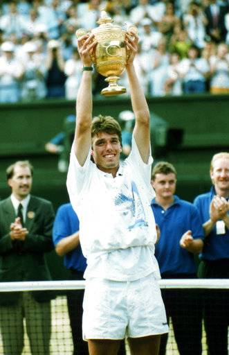 FILE - In this July 7, 1991, file photo, Wimbledon champion Michael Stich holds the trophy after beating fellow German tennis player Boris Becker in the men's singles final at Wimbledon, England. Stich and Helena Sukova have been elected to the International Tennis Hall of Fame on Wednesday, Jan. 24, 2018. The induction ceremony is scheduled for July 21. (AP Photo/Dave Caulkin, File)