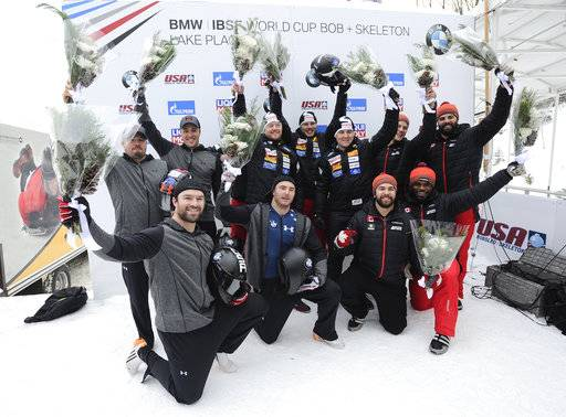 FILE - In this Dec. 17, 2016, file photo, the Swiss team of Rico Peter, Janne Bror van der Zijde, Simon Friedli and Thomas Andrianov, center rear, celebrates its win in the four-man bobsled World Cup race in Lake Placid, N.Y. The U.S. team of Steven Holcomb, rear left, Carlo Valdes, James Reed and Sam McGuffie, front left, took second place. Canada's Chris Spring, Cameron Stones, Lascelles Brown and Samuel Giguere took third place. McGuffie has scored at Notre Dame Stadium. Little did he know he was on a path to the Olympics. McGuffie was a running back at Michigan and Rice, bounced around some NFL and CFL clubs, then got told about bobsledding. Not long afterward, he met Steven Holcomb _ and this season, McGuffie's first Olympic season, has been a tribute to his late friend.(AP Photo/Hans Pennink, File)