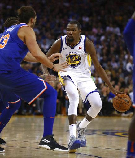 Golden State Warriors forward Kevin Durant, right, drives the ball against New York Knicks center Joakim Noah during the second half of an NBA basketball game Tuesday, Jan. 23, 2018, in Oakland, Calif. (AP Photo/Ben Margot)