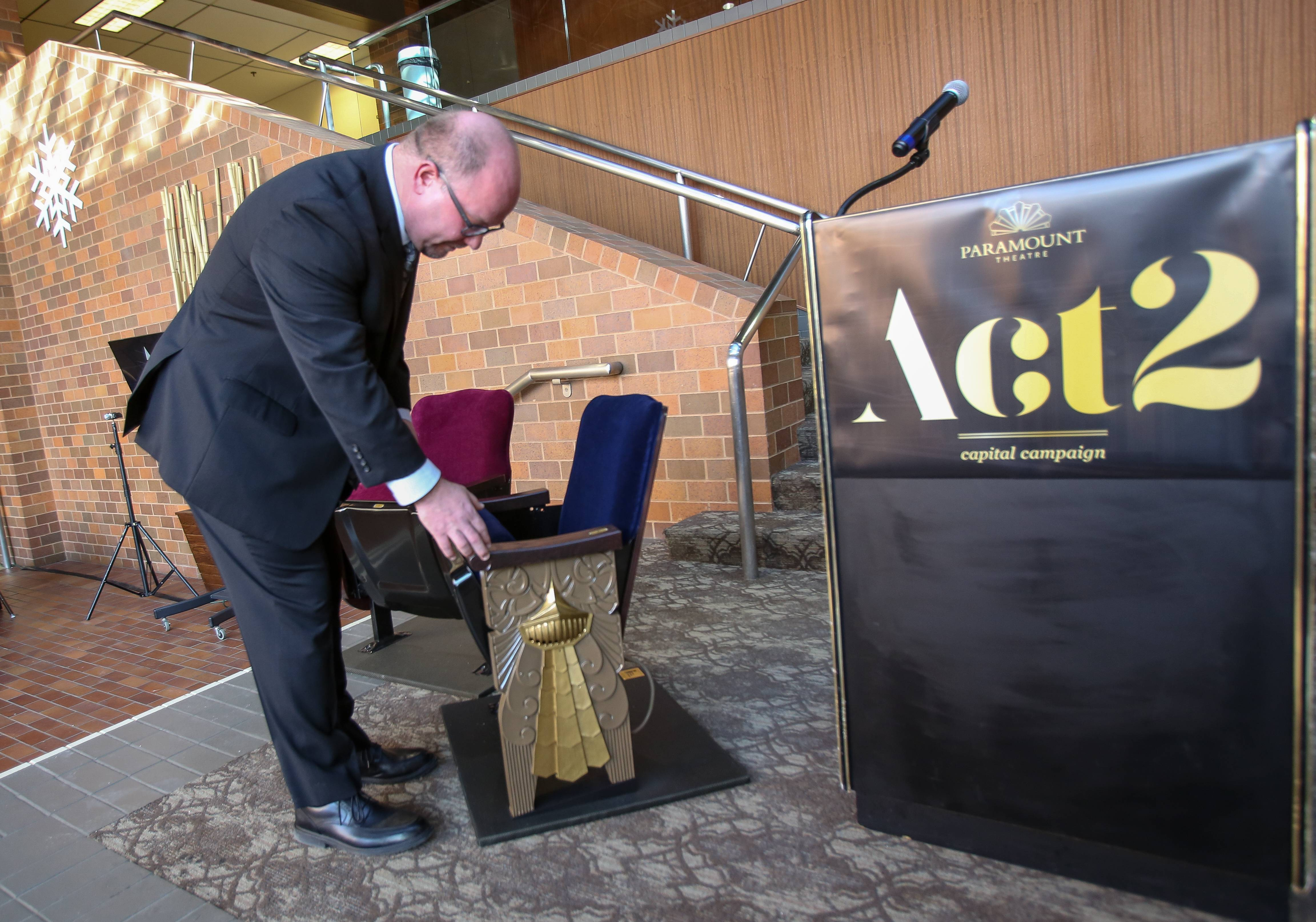 Tim Rater, president and CEO of the Paramount Theatre in Aurora, examines an old seat from the theater Thursday as supporters announce a $4.5 million capital campaign. About $1 million of the money the theater aims to raise will pay for replacement of all 1,888 seats in the 1931 theater, but the original decorative side panels will be preserved and reused.