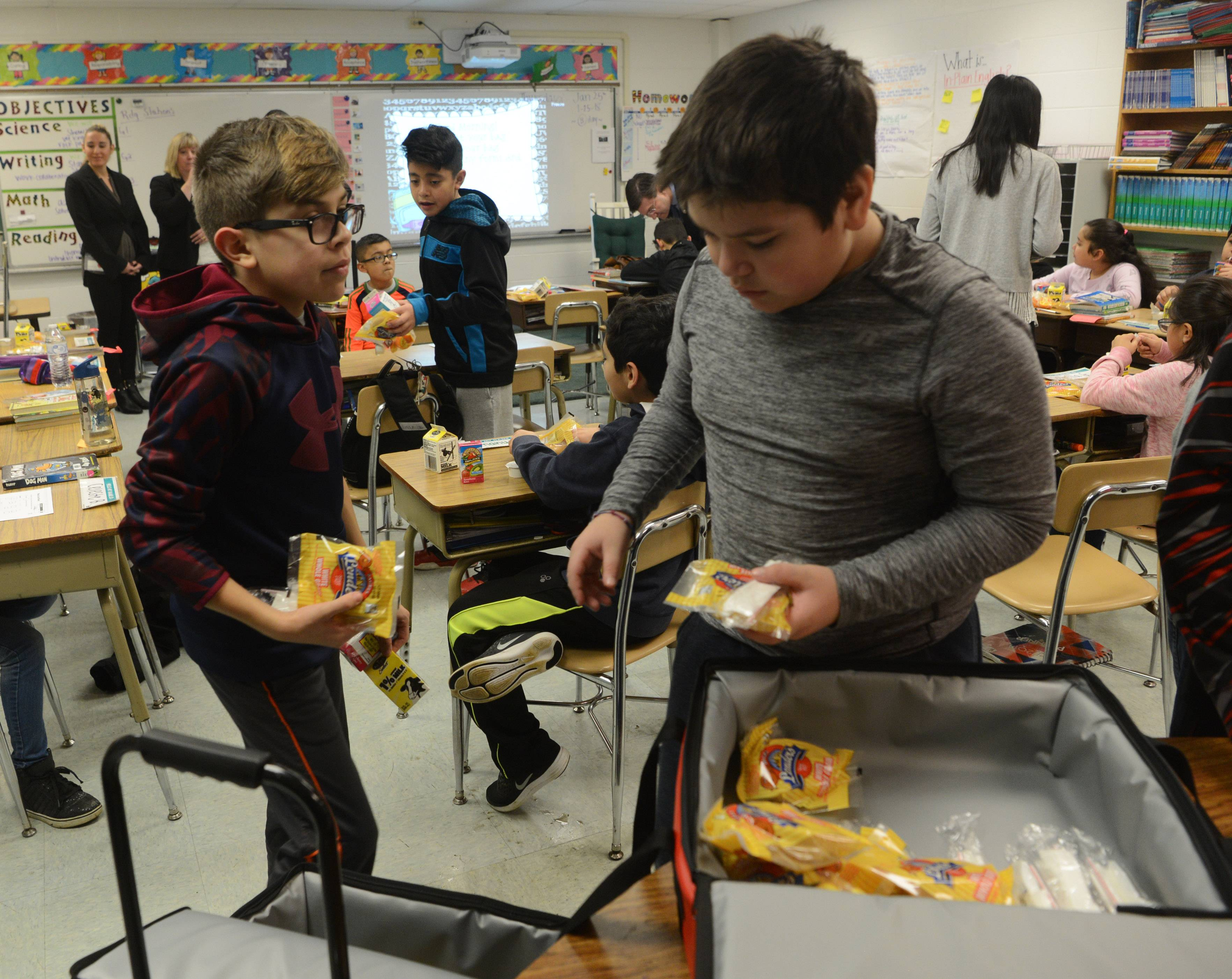 Fourth-graders John Scanlon, left, and Gabriel Reyna make their choices Thursday as part of the successful Breakfast After the Bell program at Mark Twain Elementary School in Wheeling.