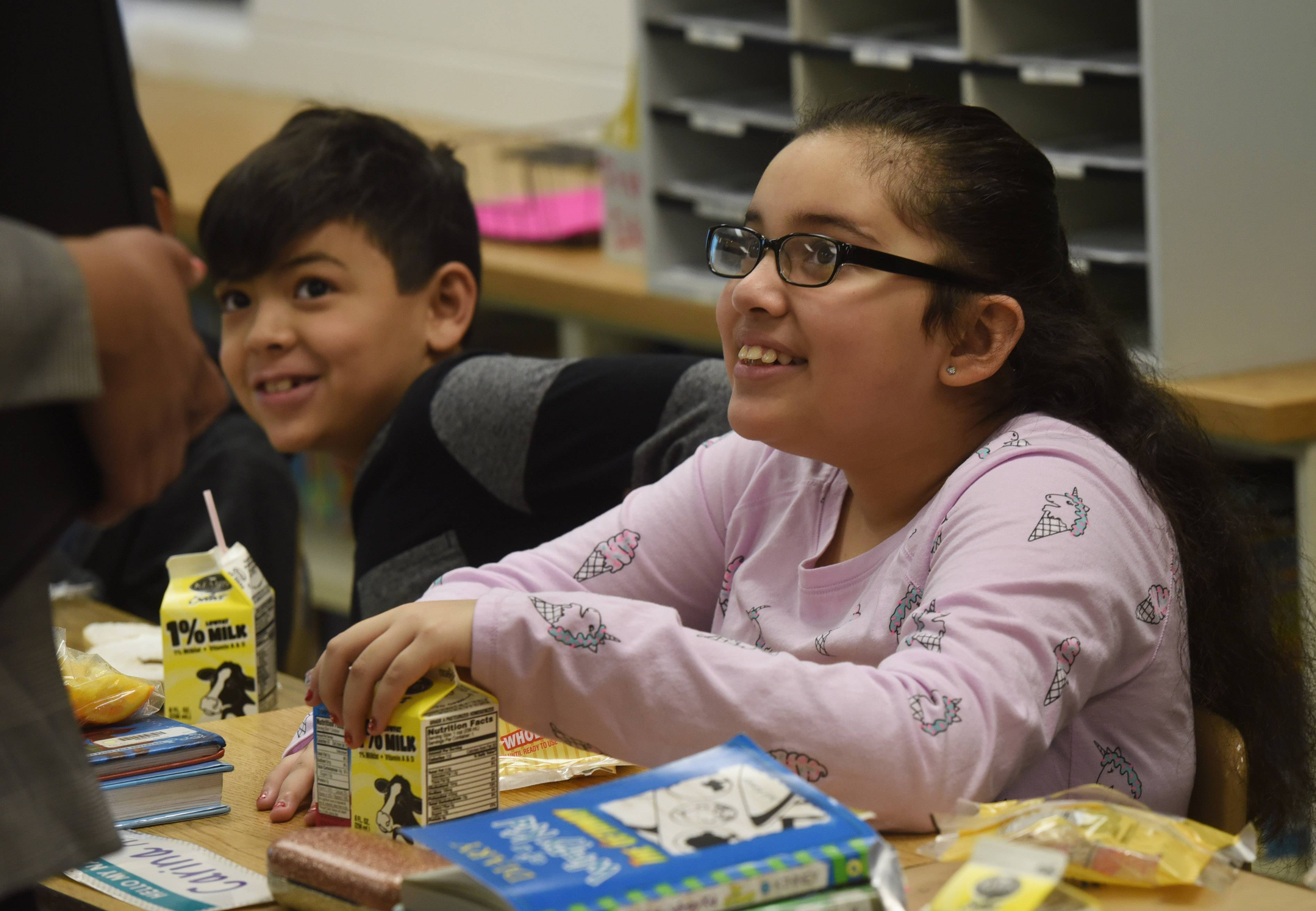 Fourth-grader Carina Aguilar chats with visitors in her classroom Thursday as the Breakfast After the Bell program is showcased at Mark Twain Elementary School in Wheeling. The breakfast was whole-grain bagels, light cream cheese, fresh orange wedges, pure strawberry-kiwi juice and milk.