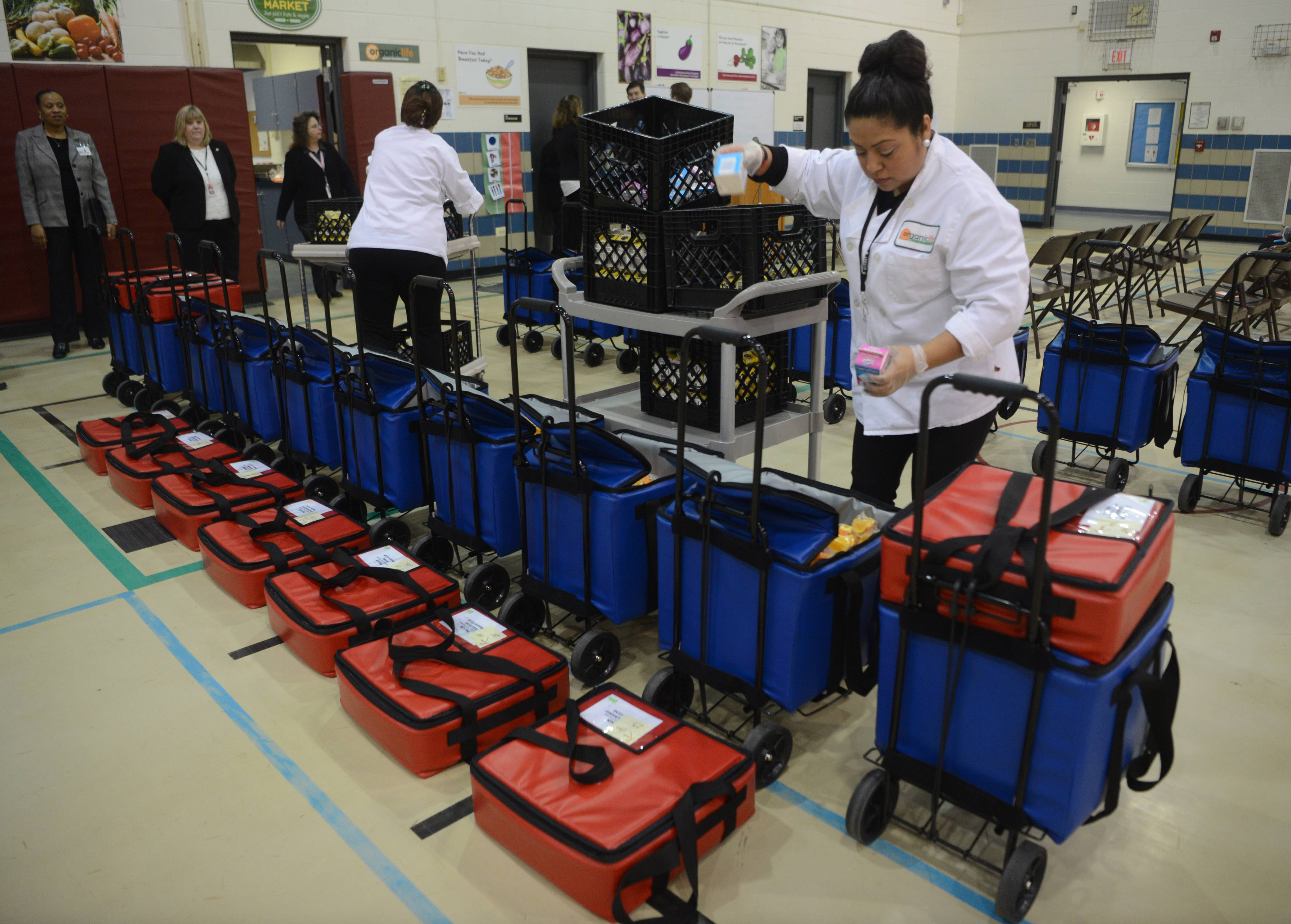 Food service worker Hanny Macedo packs carriers for the Breakfast After the Bell program Thursday at Mark Twain Elementary School in Wheeling.