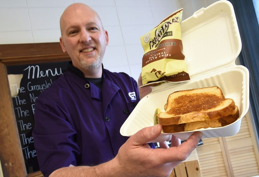 Paul Patricelli, co-owner of GRIL restaurant, holds the Grayslaker gourmet grilled cheese sandwich. The eatery moved from Mundelein to Grayslake.