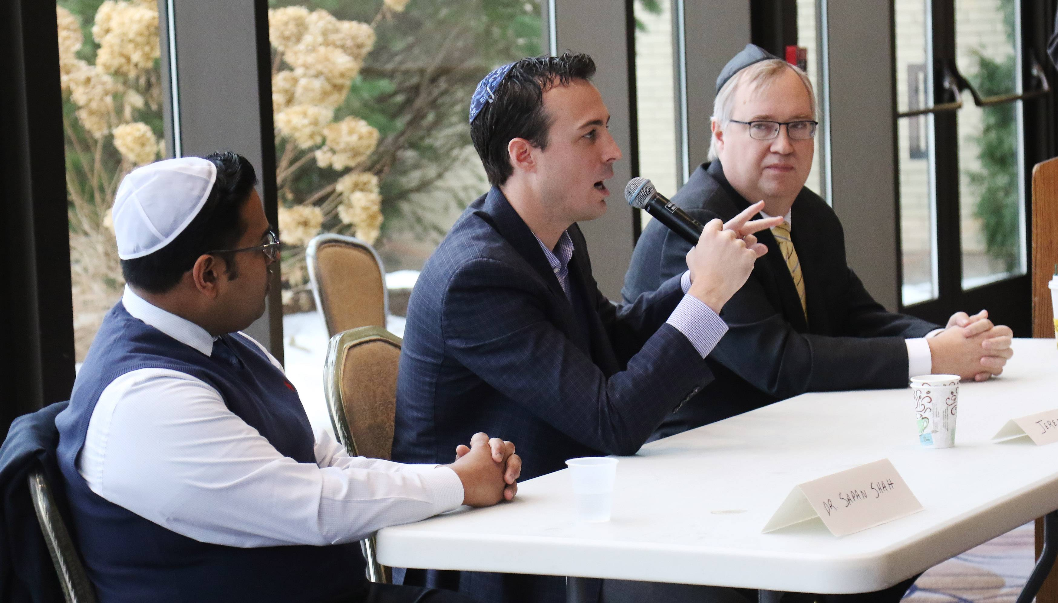 Republican congressional candidate Jeremy Wynes, center, talks while fellow candidates Dr. Sapan Shah, left, and Douglas Bennett listen during a recent political forum at a Highland Park synagogue.