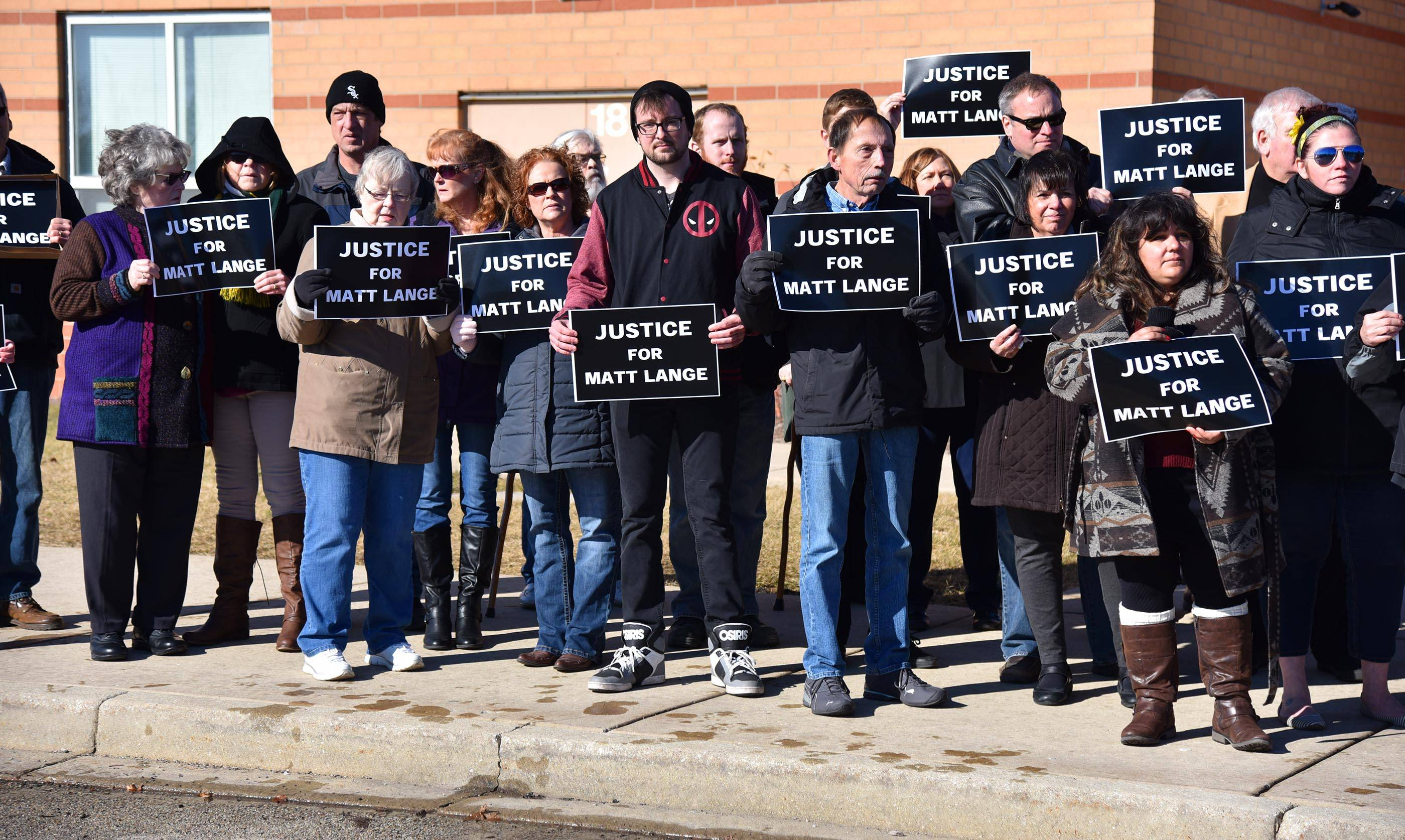 "Supporters hold signs for the assembled news media reading ""Justice for Matt Lange"" Saturday at Scullen Middle School at a memorial event for Lange, who was murdered in his car at this location one year ago in Naperville."