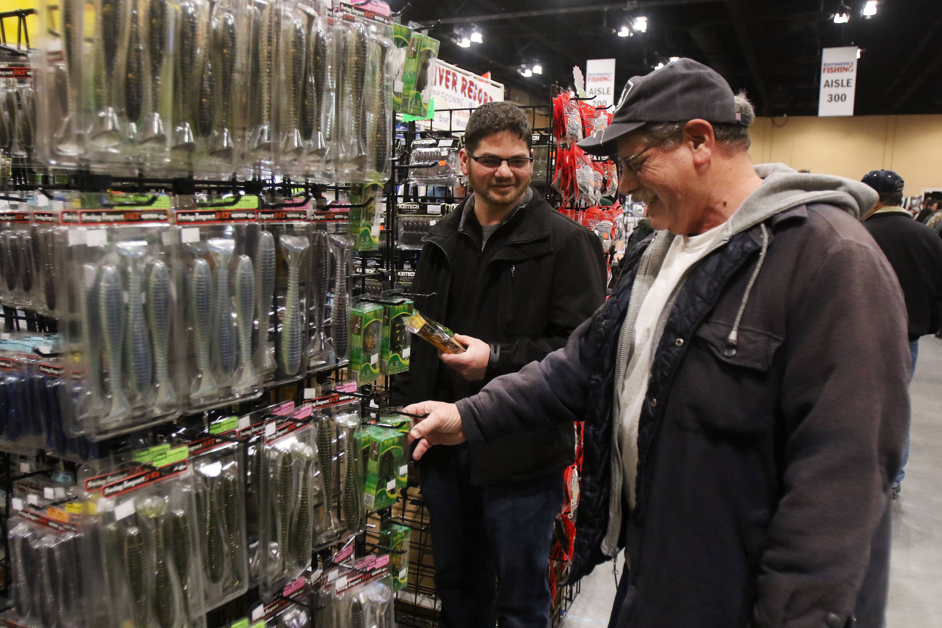Bradley Paulus of Mount Prospect, left, talks to his dad, Cliff, about lures Sunday at the Anglers International Resources booth during the 6th Annual Chicagoland Fishing, Travel & Outdoor Expo at the Schaumburg Convention Center.