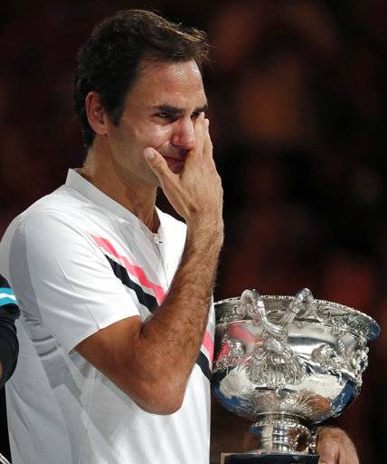 Switzerland's Roger Federer wipes tears away from his eyes as he holds his trophy after defeating Croatia's Marin Cilic during the men's singles final at the Australian Open tennis championships in Melbourne, Australia, Sunday, Jan. 28, 2018.