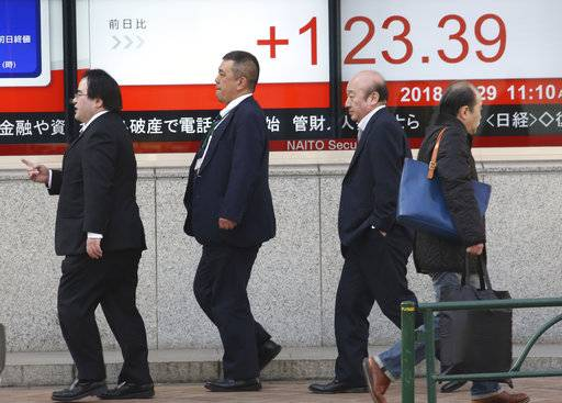 People walk by an electronic stock board of a securities firm in Tokyo, Monday, Jan. 29, 2018. Asian shares were mixed Monday after several markets ceded gains from upbeat openings that tracked Friday's rally on Wall Street.