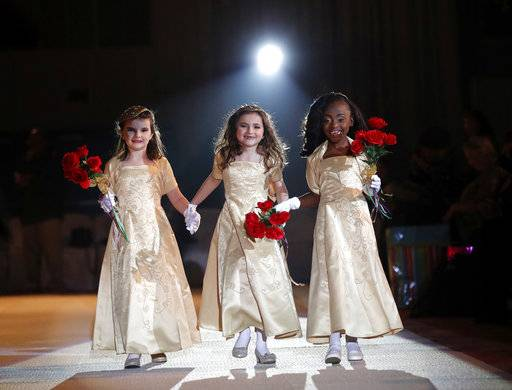 The ladies in waiting of the royal court of the Krewe of Little Rascals walk for the audience during their Mardi Gras Ball in Kenner, La., Thursday, Jan. 25, 2018. The more than 200 kids riding in Sunday's Mardi Gras parade participated in a glitzy ball held in their honor.