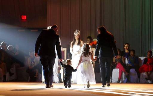 Junior members of the royal court are escorted to the last year's king and queen during the Little Rascals Mardi Gras Ball in Kenner, La., Thursday, Jan. 25, 2018.