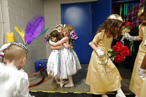 Children in the royal court share a group hug backstage before the start of the Little Rascals Mardi Gras Ball in Kenner, La., Thursday, Jan. 25, 2018.