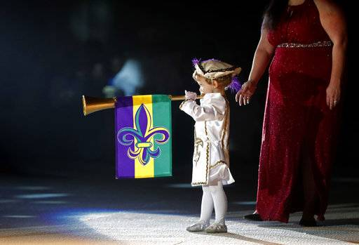 Royal court troubadour Andrew Perret heralds the king and queen at the Little Rascals Mardi Gras Ball in Kenner, La., Thursday, Jan. 25, 2018. The weeks-long celebration leading up to Fat Tuesday is often perceived as an adults-only holiday in the French Quarter's famed Bourbon Street festivities. But elsewhere, children and families are as much a part of the revelry as anyone.