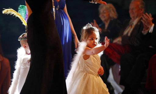 Charlee Gonzalez, 2, a member of the royal court, waves to the audience during the Little Rascals Mardi Gras Ball in Kenner, La., Thursday, Jan. 25, 2018.