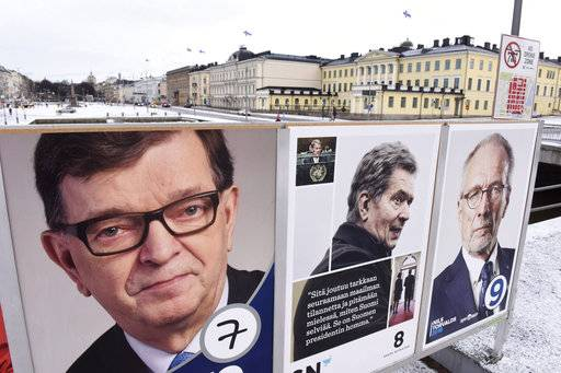 Campaign posters of Finnish presidential candidates are displayed in front of the presidential palace in Helsinki, Finland, Sunday, Jan. 28, 2018. Finns are voting for a new president in the election that's expected to see the highly popular incumbent score a win during Sunday's first round. (Heikki Saukkomaa/Lehtikuva via AP)