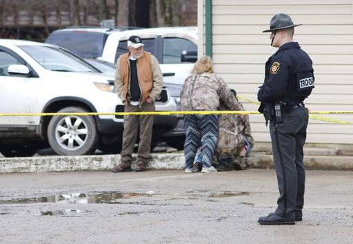 An officer stands guard as people comfort each other near the scene of a fatal shooting at a car wash in Melcroft, Pa., Sunday, Jan. 28, 2018. (Michael Palm /Herald-Standard via AP)