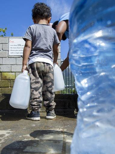 "People queue to collect water from a natural spring outlet in the South African Breweries in Cape Town, Tuesday Jan. 23, 2018.  A harsh drought may force South Africa's showcase city of Cape Town to turn off most of its taps, as the day that the city runs out of water, ominously known as ""Day Zero"" moves ever closer for the nearly 4 million residents."