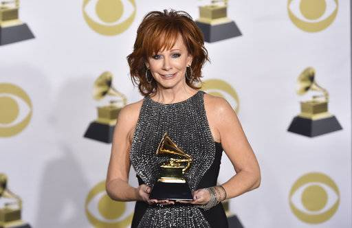 "Reba McEntire poses in the press room with the best roots gospel album award for ""Sing It Now: Songs Of Faith & Hope"" at the 60th annual Grammy Awards at Madison Square Garden on Sunday, Jan. 28, 2018, in New York. (Photo by Charles Sykes/Invision/AP)"