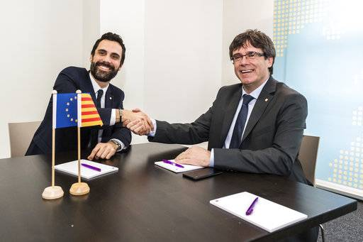 Ousted Catalan leader Carles Puigdemont, right, shakes hands with the President of the Parliament of Catalonia Roger Torrent in Brussels on Wednesday, Jan. 24, 2018.